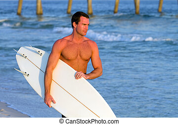 Surfer Carrying Surfboard - Young athletic adult male surfer...