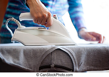 Womans hands ironing - Closeup on womans hands ironing, with...