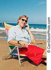 Business man calling by cell phone at the beach