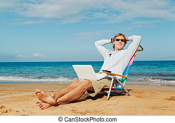 Young Attractive Man Relaxing at the Beach with Laptop...
