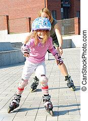 city park family rolleblading on roller skates together -...