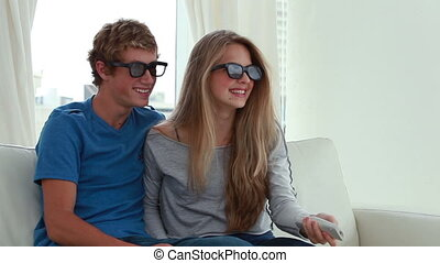 Happy couple wearing 3d glasses in front of the television...