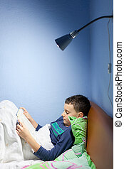 Kid reading a book at bedtime - Portrait of a boy reading a...