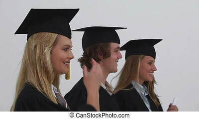 Smiling friends being graduated together against a grey...