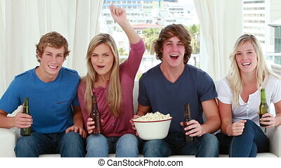 Happy friends eating popcorn while sitting in the living...