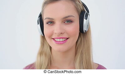 Happy woman listening to music while laughing against a...