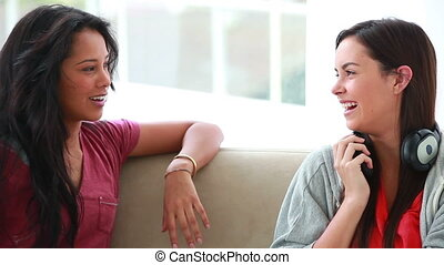Smiling young women talking to each other in the living room
