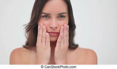 Peaceful woman massaging her cheeks