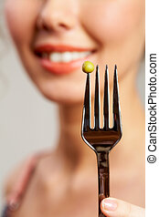 Pea on fork - Close-up of fork with pea held by smiling girl