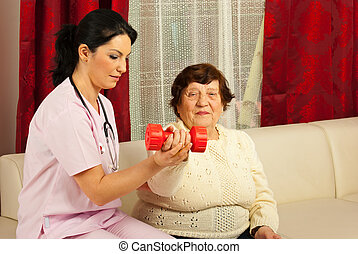 Therapist helping senior to do exercises - Therapist woman...