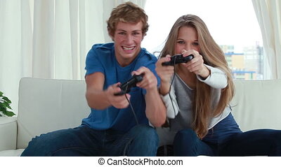 Smiling couple playing video games together in the living...