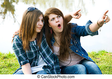 Two surprised young teens on the lake