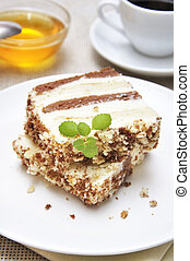 Sweet dessert Two slices of cake on white plate with cup of...