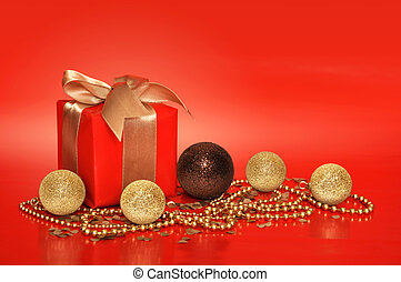 Red gift box with golden ribbon and cristmas decoration on...