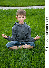 yoga boy - eight years old boy practices yoga outdoors