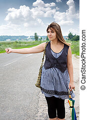 Hitchhiking Girl - Beautiful young brunette woman...