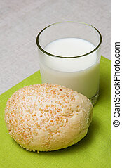 milk and bread roll - Glass of milk with brad roll on a...