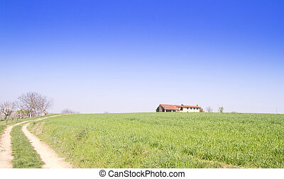 Landscape of a green hill under the blue sky, with a farm