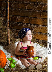 little girl sits on a mow with a jug of milk in hands