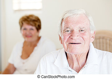 senior man and his wife in background
