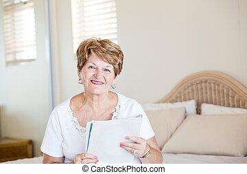 happy senior woman reading newspaper