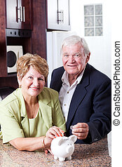 retirement savings concept: senior couple putting coins in...