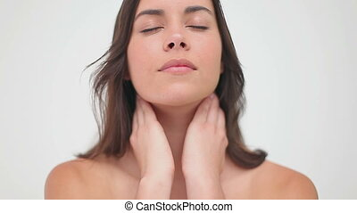 Peaceful woman rubbing her neck against a white background