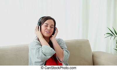 Happy brunette woman sitting while listening to music in her...