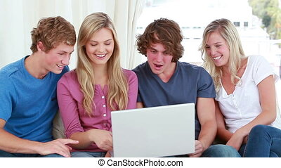 Happy friends laughing while looking at a laptop