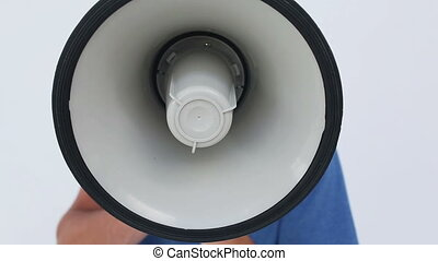 Angry young man using a megaphone against a white background