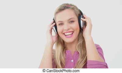 Smiling blonde woman wearing headphones against a white...