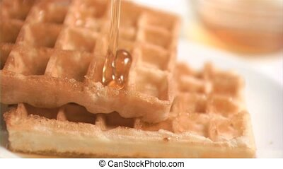 Honey falling in super slow motion on waffles