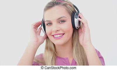 Happy blonde woman listening to music against a white...