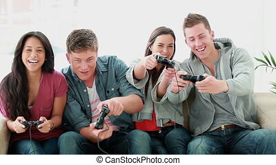 Friends playing video games while laughing in the living...