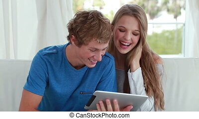 Couple looking at an ebook together in the living room