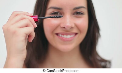 Happy brunette woman using mascara against a white...