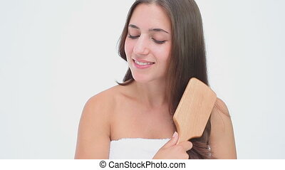 Smiling woman brushing her long hair against a white...