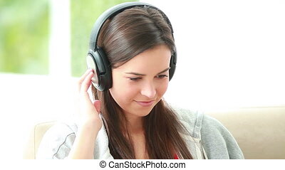 Smiling brunette woman listening to music with headphones in...