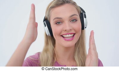 Blonde woman dancing while listening to music against a...