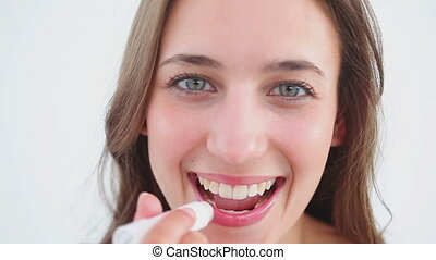 Cheerful woman using lip balm on her lips against a white...