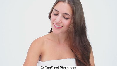Smiling woman brushing her brown hair against a white...