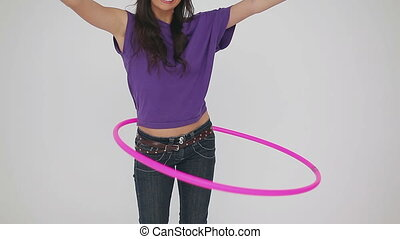 Cheerful woman playing with a hula hoop