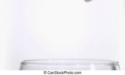 Ice cubes in super slow motion falling together against a...