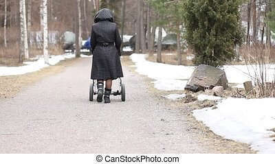Someone walking a baby in a stroller on a gravel road