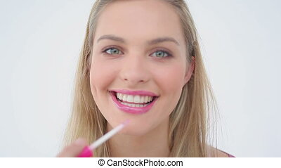 Smiling blonde woman applying lip gloss on her lips against...