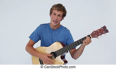 Smiling brunette man playing the guitar against a white...