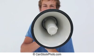 Serious man shouting into a megaphone against a white...