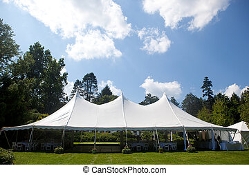 wedding tent with blue sky - A large white wedding tent set...
