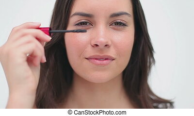 Happy woman using mascara on her eyelashes against a white...