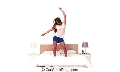 Woman bouncing in slow motion on her bed